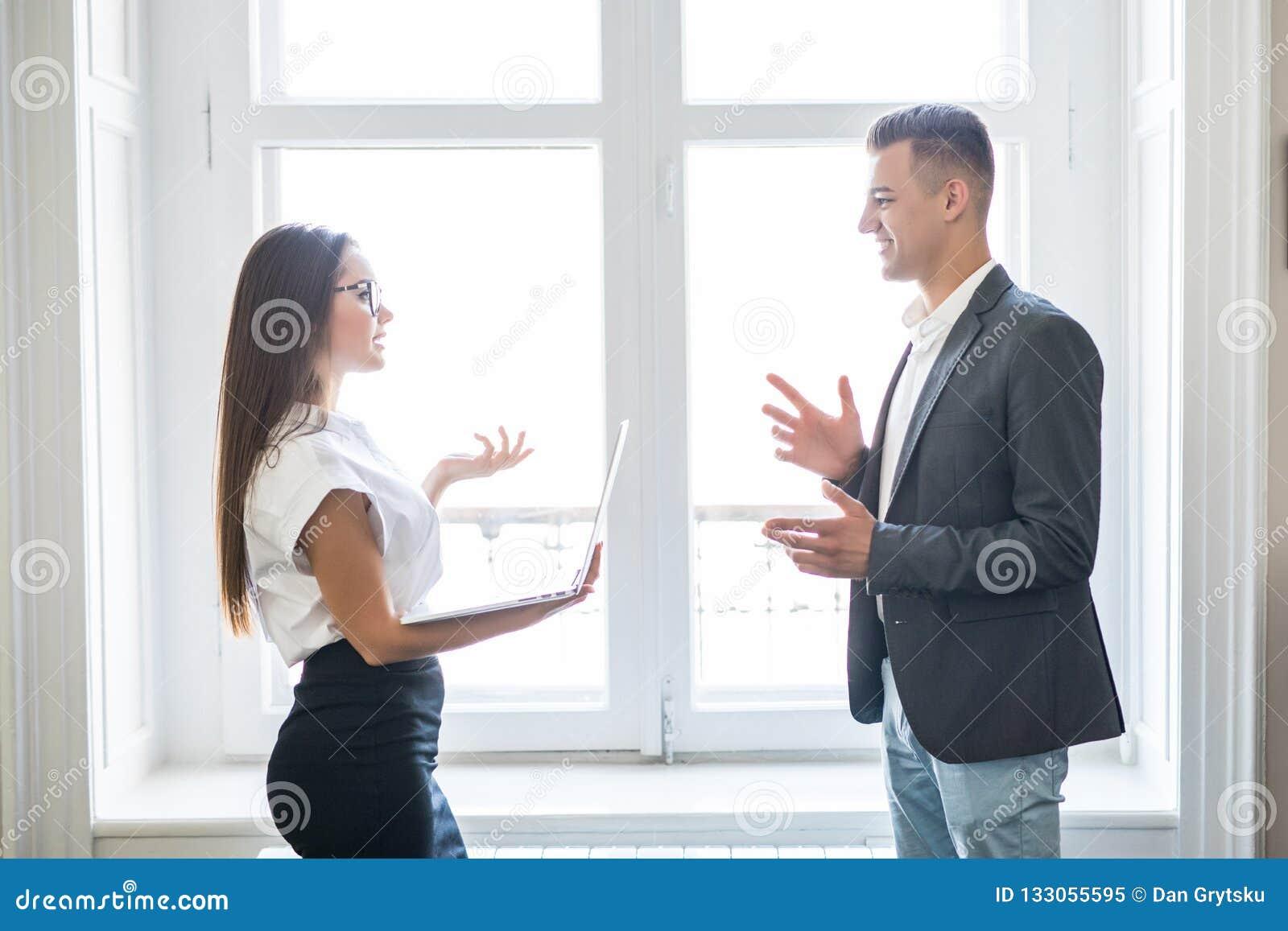L homme d affaires et la femme d affaires discutent informel près des fenêtres d immeuble de bureaux