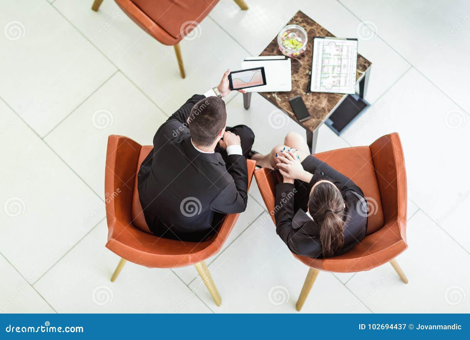 L homme d affaires et la femme d affaires s asseyant dans des fauteuils passent en revue la documentation, vue supérieure