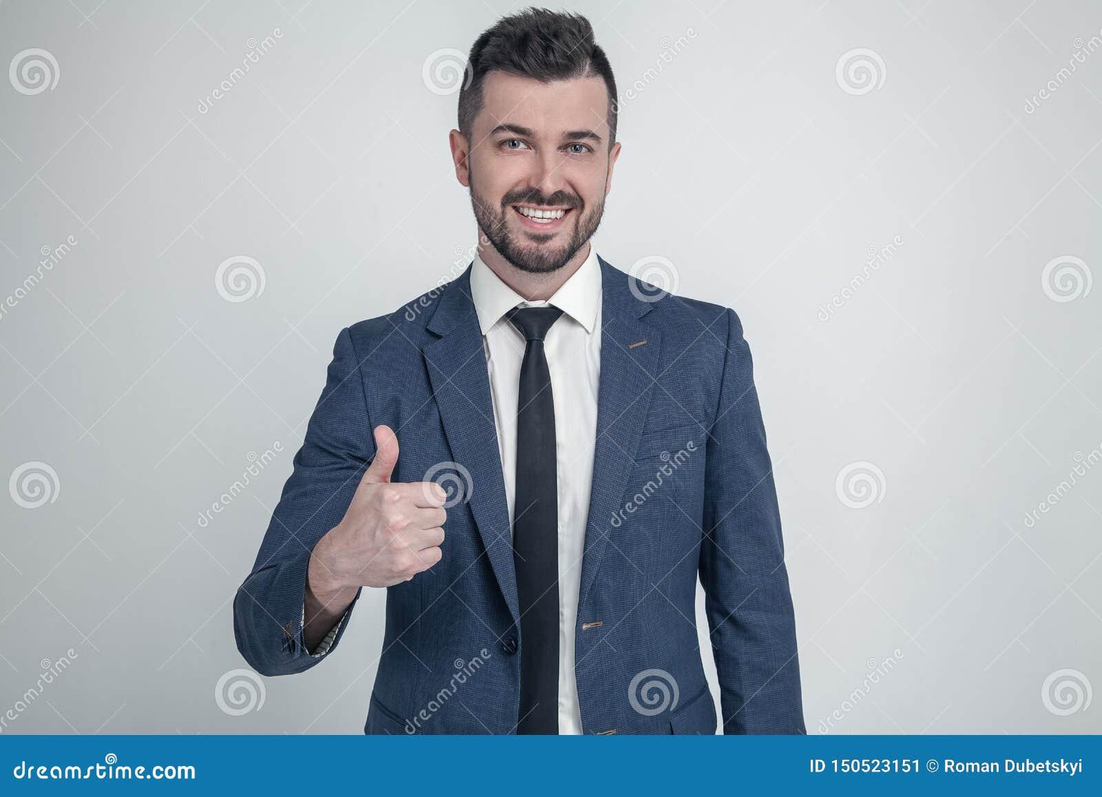 L homme d affaires gai manie maladroitement vers le haut de la pose et du sourire ? l appareil-photo habillé dans un costume clas