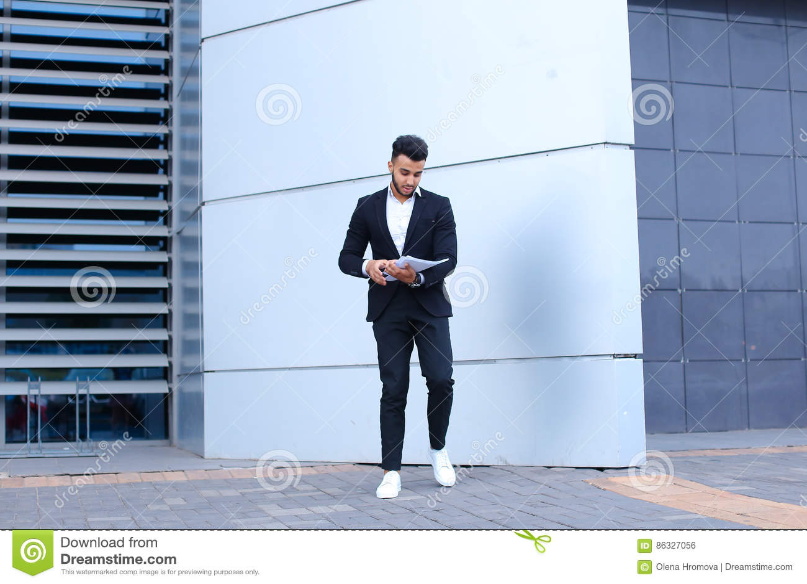 L homme d affaires masculin arabe d homme rassemble des papiers et des documents près d o