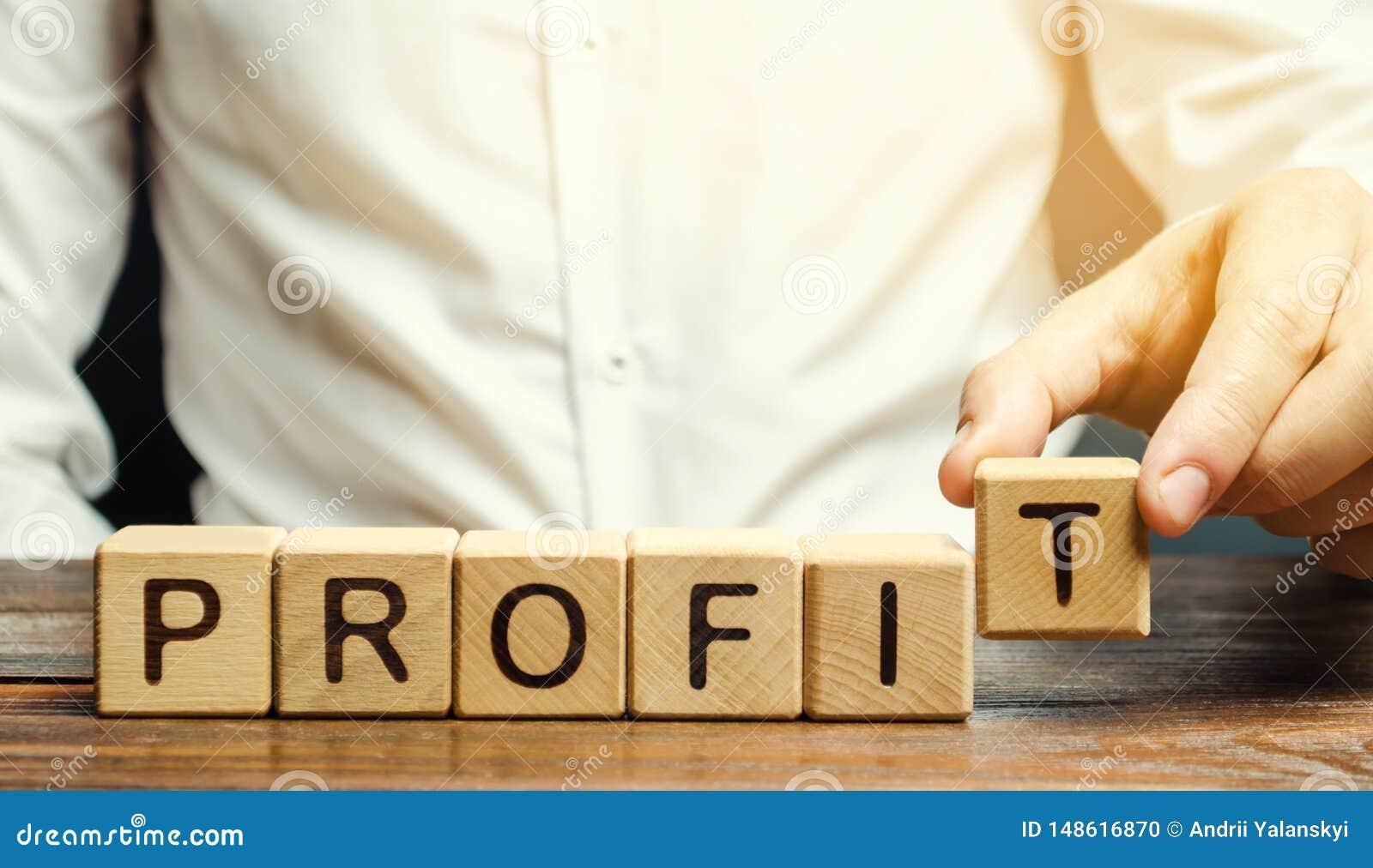 L homme d affaires met les blocs en bois avec le bénéfice de mot Le bilan financier de la société pendant une certaine période pr