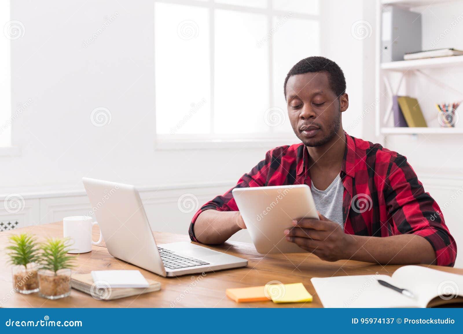 L homme d affaires noir dans le bureau occasionnel travaillent
