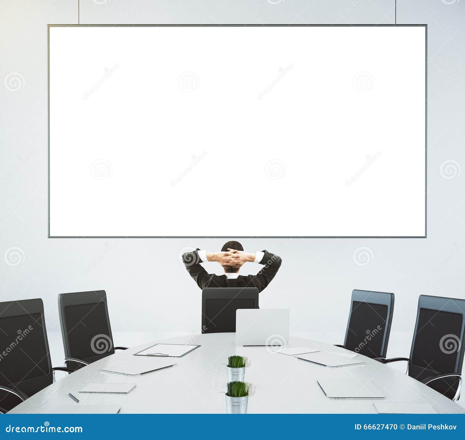 L homme d affaires regarde l affiche vide sur le mur dans moderne conferen