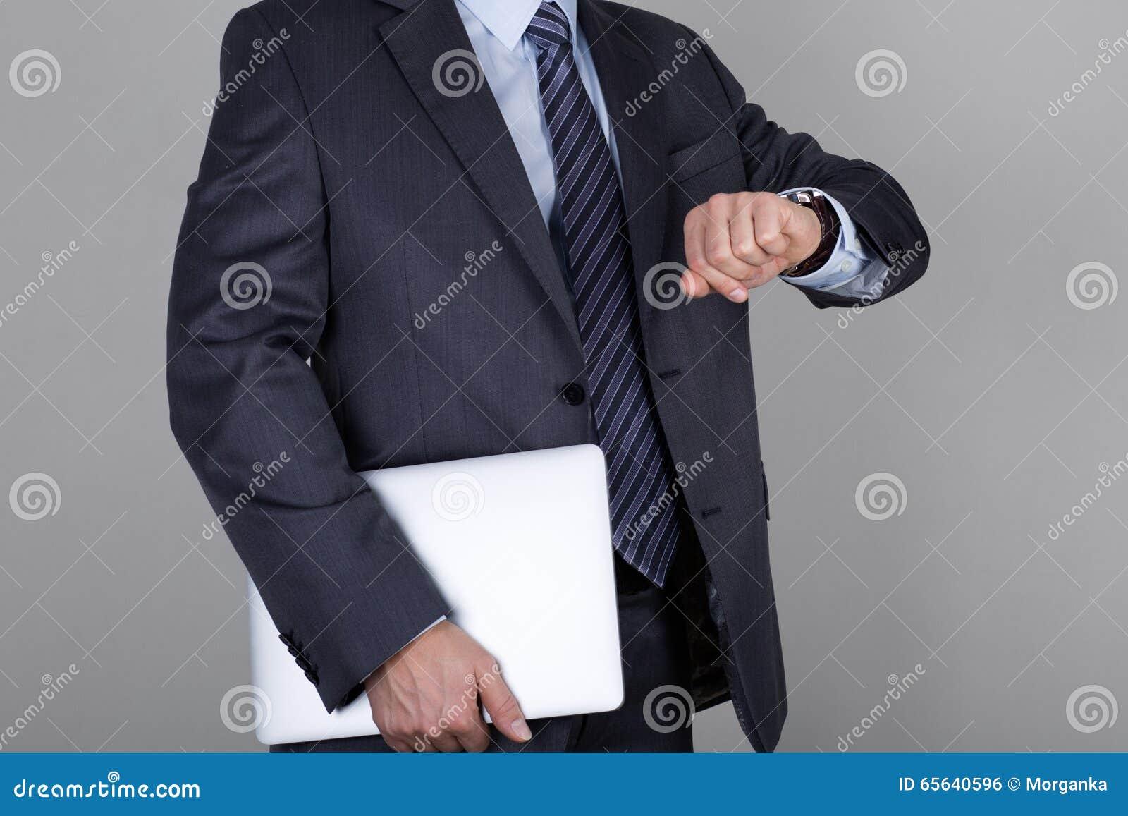 L homme d affaires regarde sa montre-bracelet vérifiant le temps