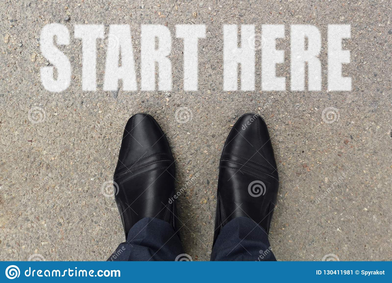 L homme d affaires regarde vers le bas ses pieds sur un plancher en béton avec des lettres de DÉBUT ICI peintes sur la surface Im