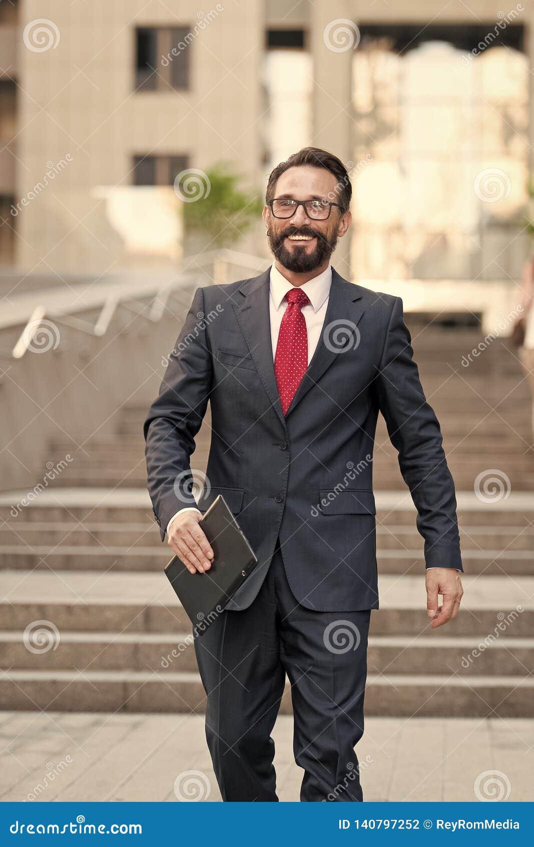 L homme d affaires se tient à l immeuble de bureaux avec le comprimé à disposition la personne habillée dans le costume et la che