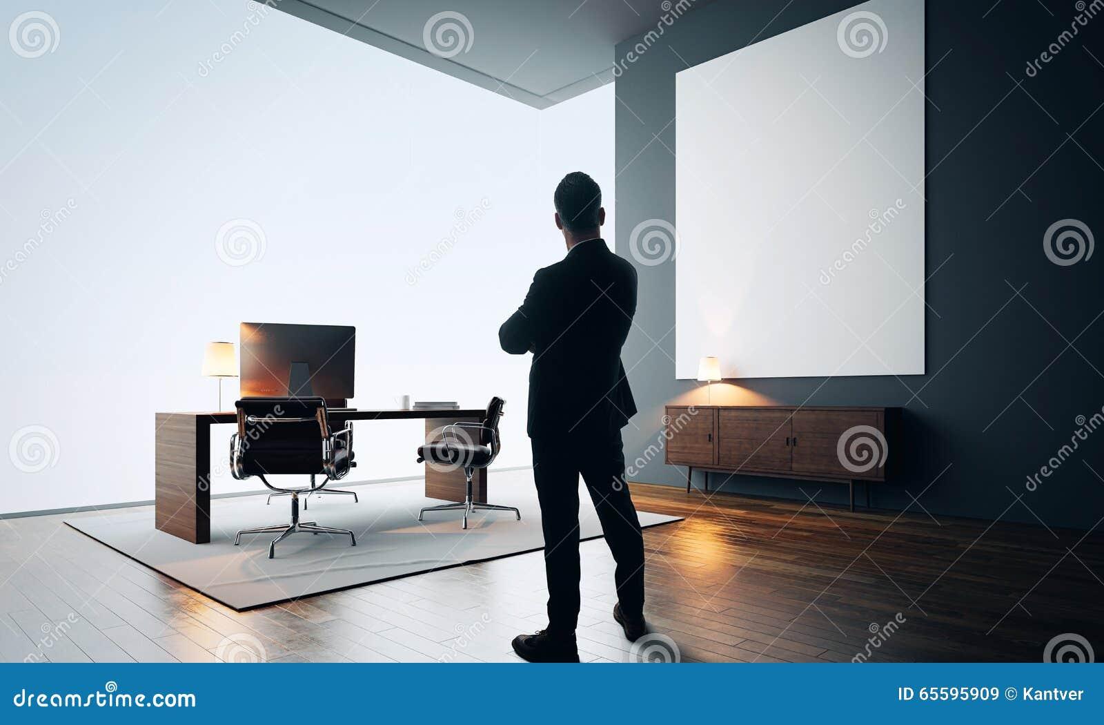 L homme d affaires se tient dans le bureau moderne avec la toile
