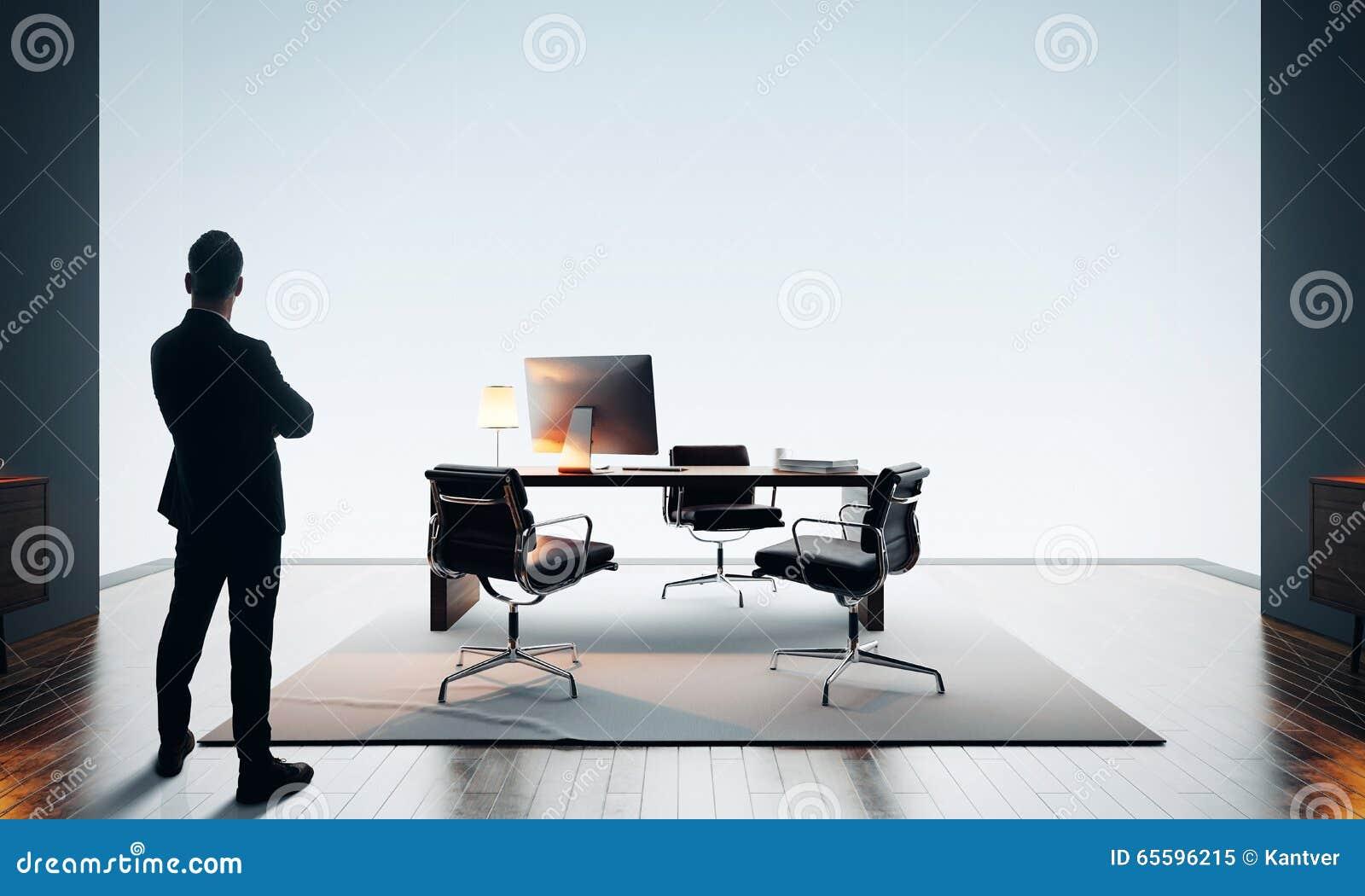 L homme d affaires se tient le bureau moderne et en regardant l