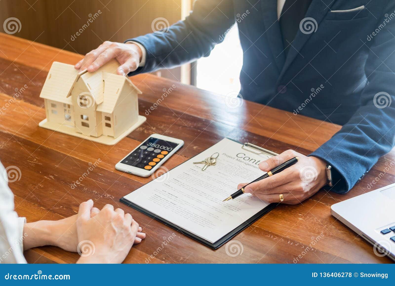 L homme d affaires signe le contrat derrière le modèle architectural à la maison Discussion avec un staffde location de société