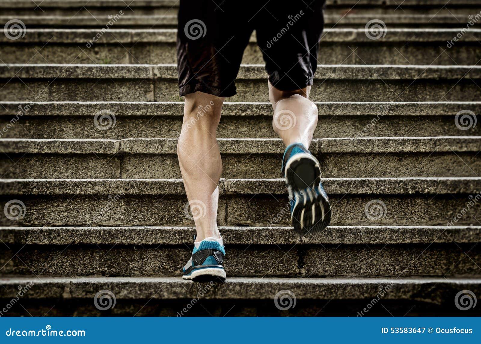 L homme d athlète avec la jambe forte muscles l escalier urbain de ville de formation et de fonctionnement dans la forme physique