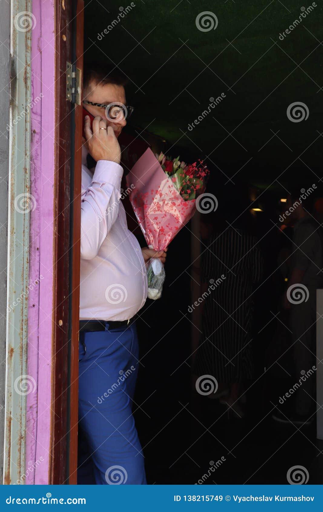 L homme dans l amour avec un grand bouquet des fleurs, parle avec son aimé au téléphone