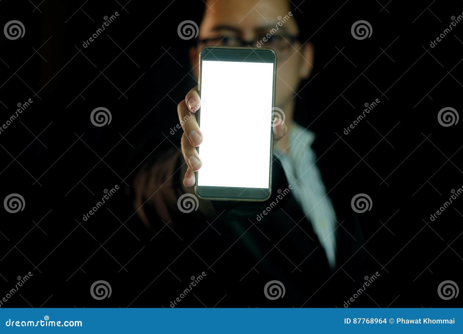 L homme dans l obscurité montre le téléphone intelligent