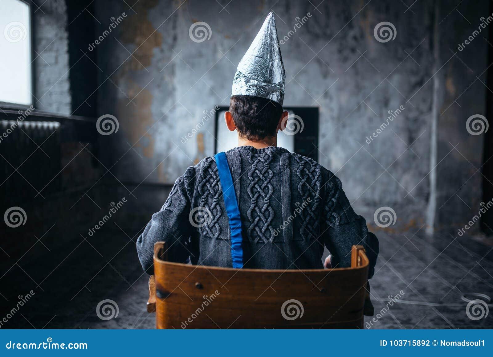 L homme dans le casque de feuille d étain regarde TV, phobie d UFO