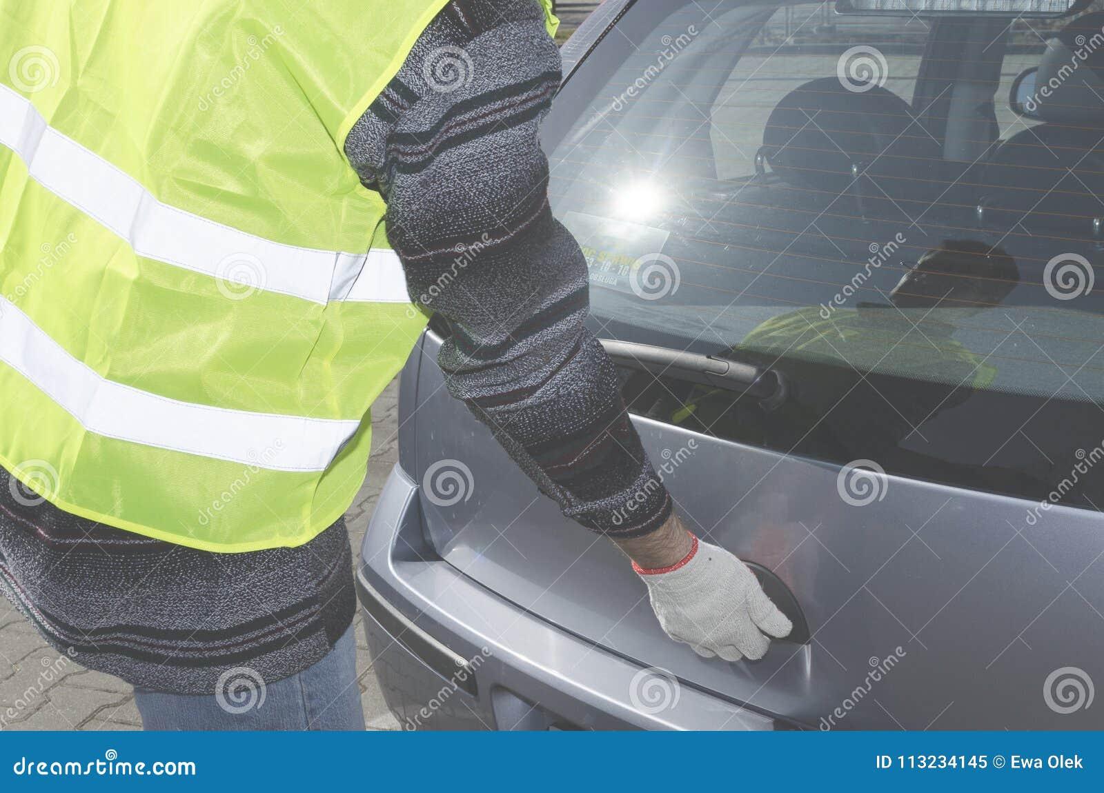 L homme dans un gilet de sécurité ouvre la botte dans sa voiture