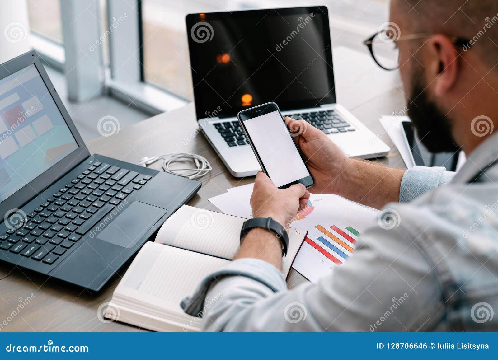 L homme de hippie s assied en café, utilise le smartphone, travaille sur deux ordinateurs portables L homme d affaires lit un mes