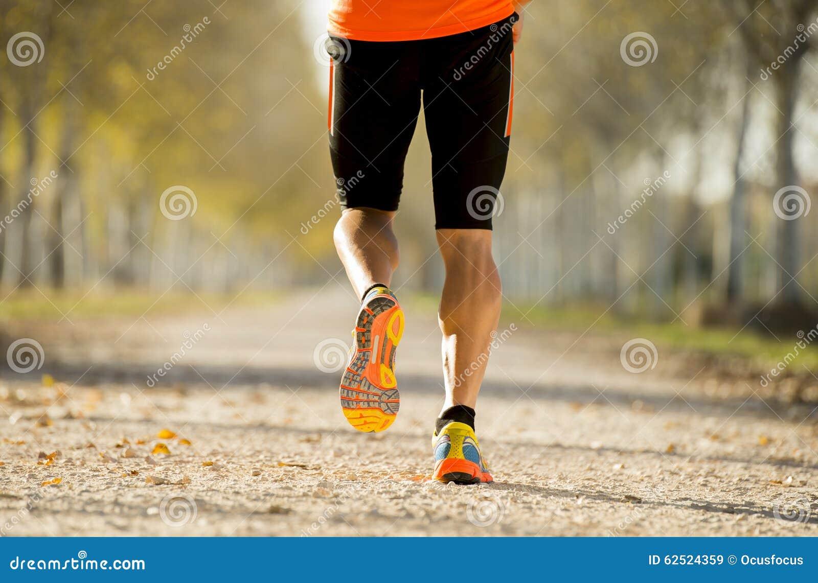 L homme de sport avec le muscle fort de veaux fonctionnant dehors dans outre de la traînée de route a rectifié avec des arbres so