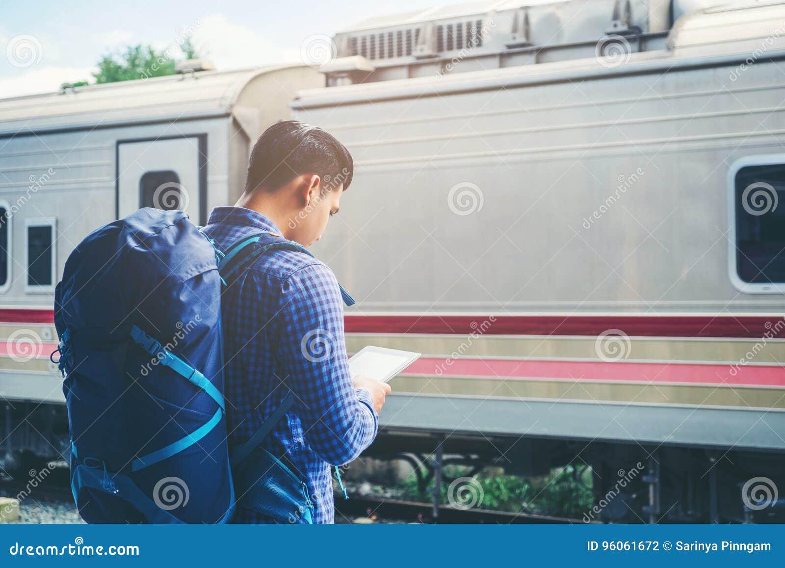 L homme de voyageur à l aide du comprimé et les attentes s exercent sur la plate-forme ferroviaire