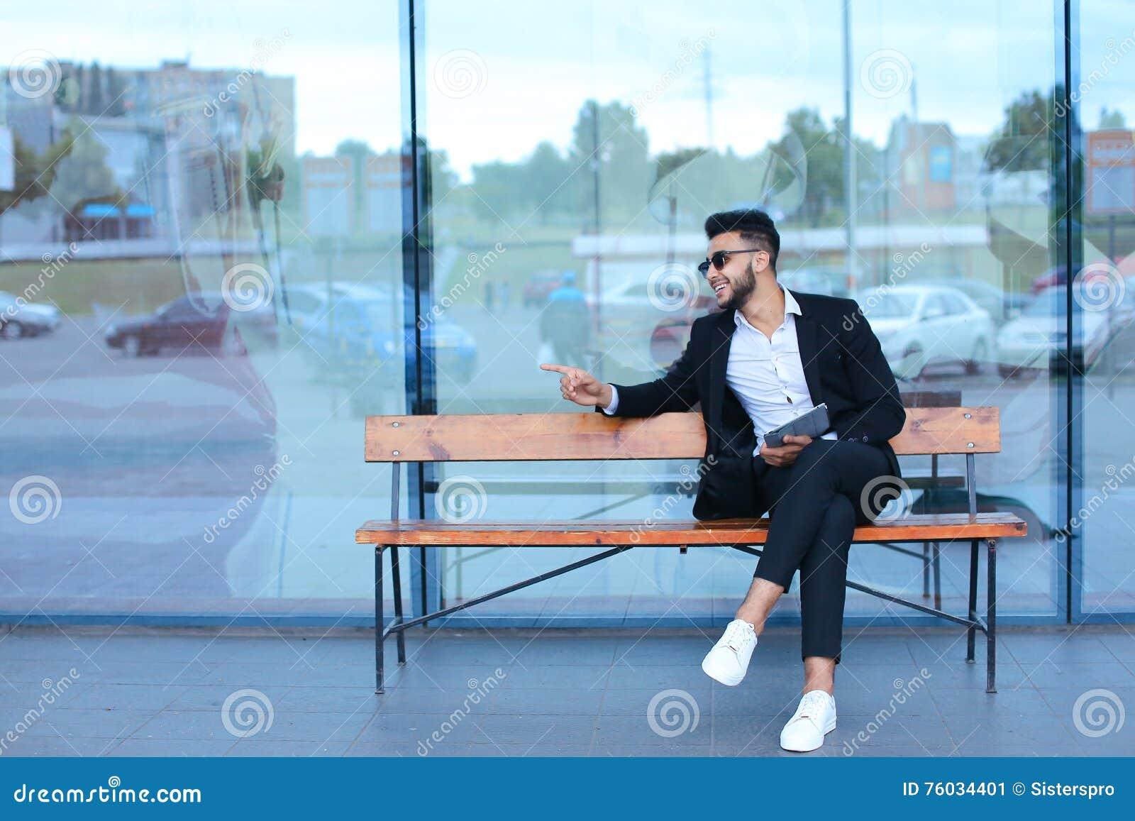 L homme en arabe de costume met dessus des lunettes de soleil avec