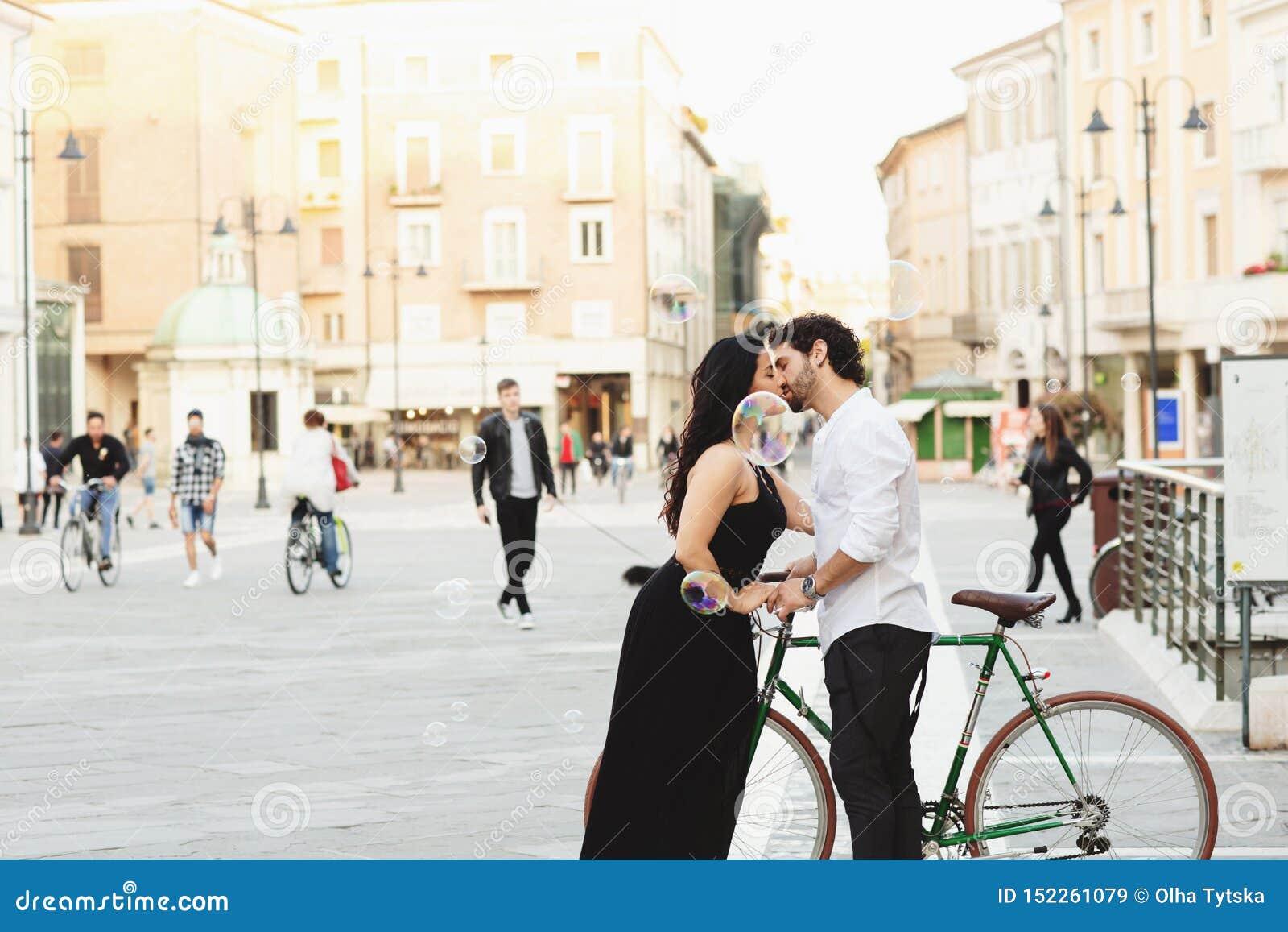 L homme et la femme avec une bicyclette embrassent dans la vieille ville Autour de eux sont les bulles de l eau Histoire d amour