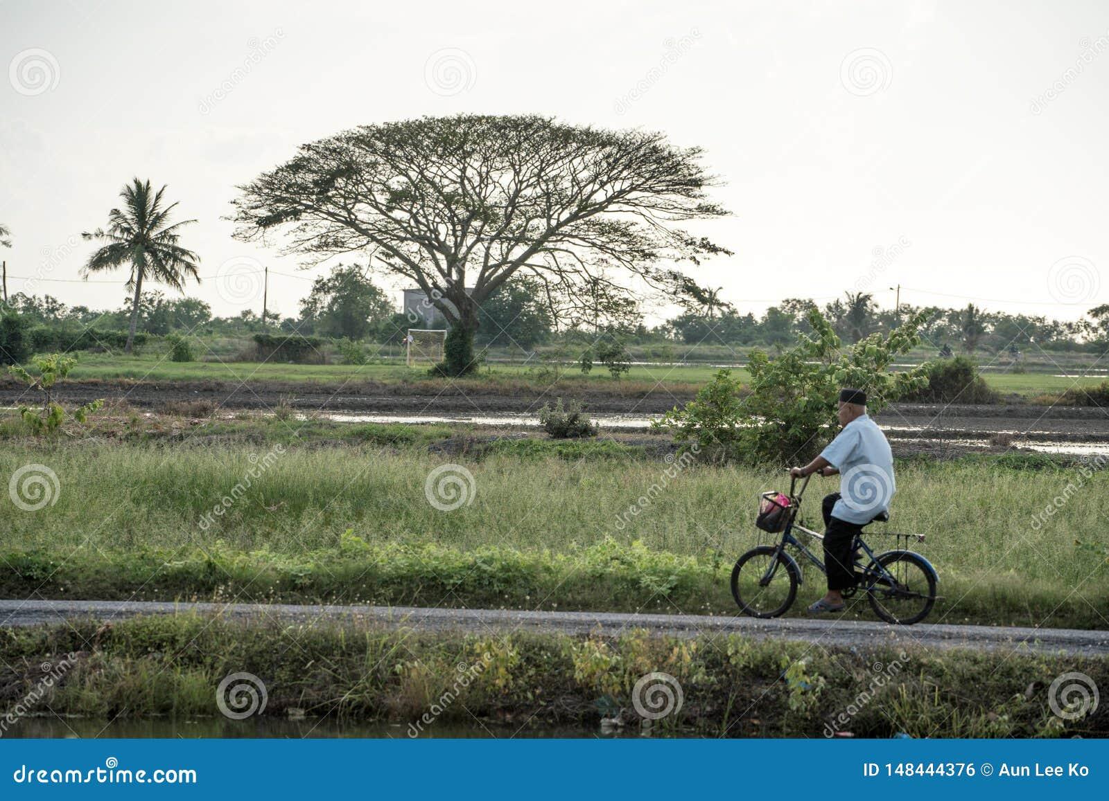 L homme faisant un cycle par le village