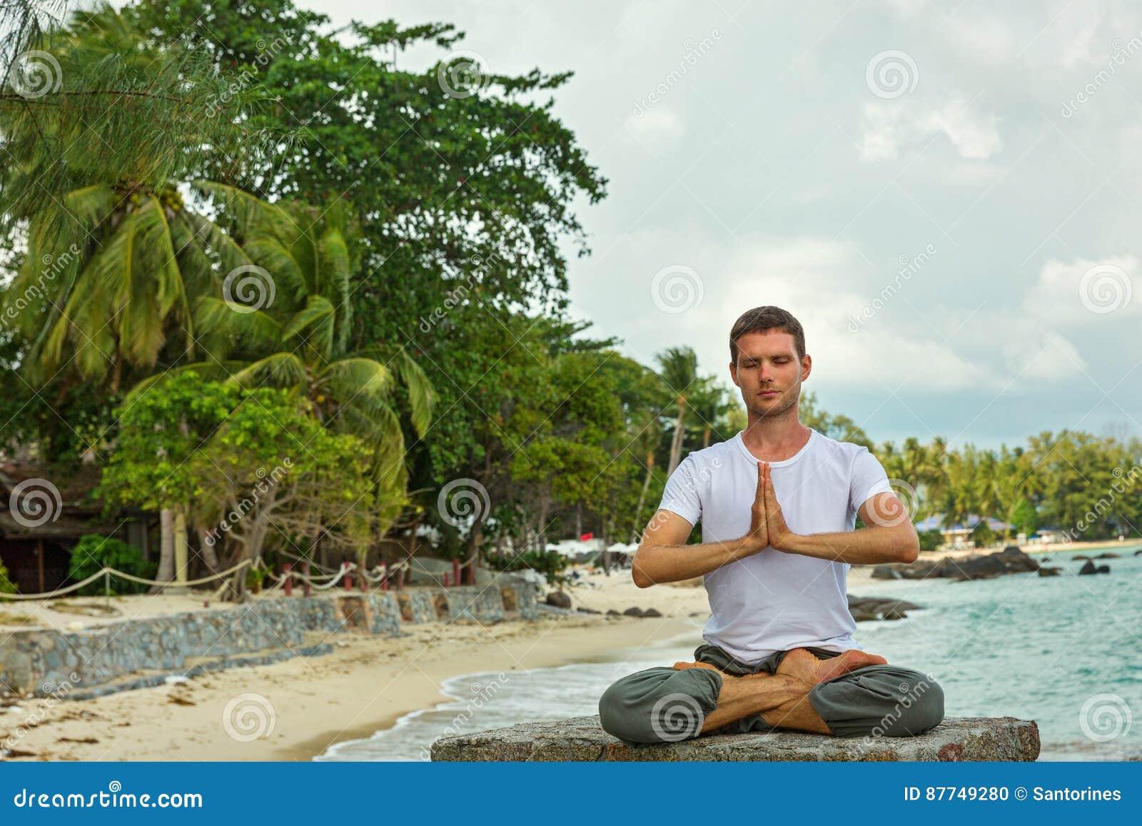 l 39 homme fait le yoga sur la plage photo stock image 87749280. Black Bedroom Furniture Sets. Home Design Ideas