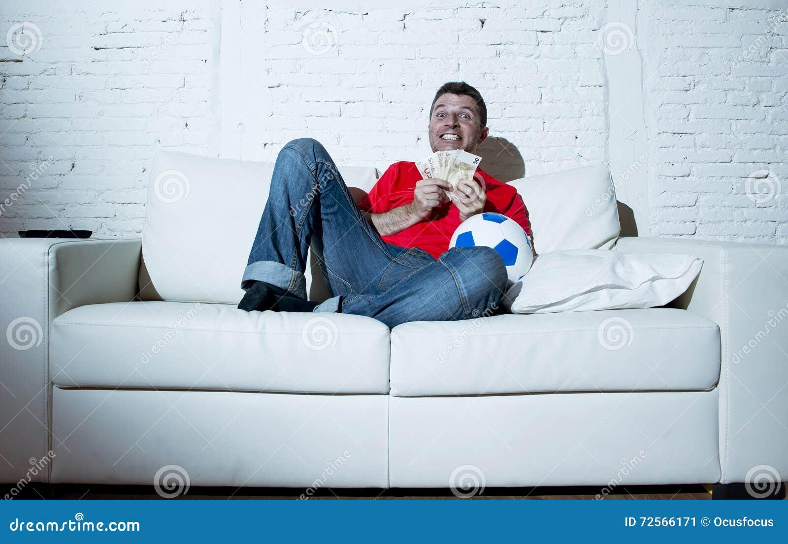 L homme fol tenant le football de observation d argent et de ballon de football sur l Internet de TV en ligne a parié le jeu