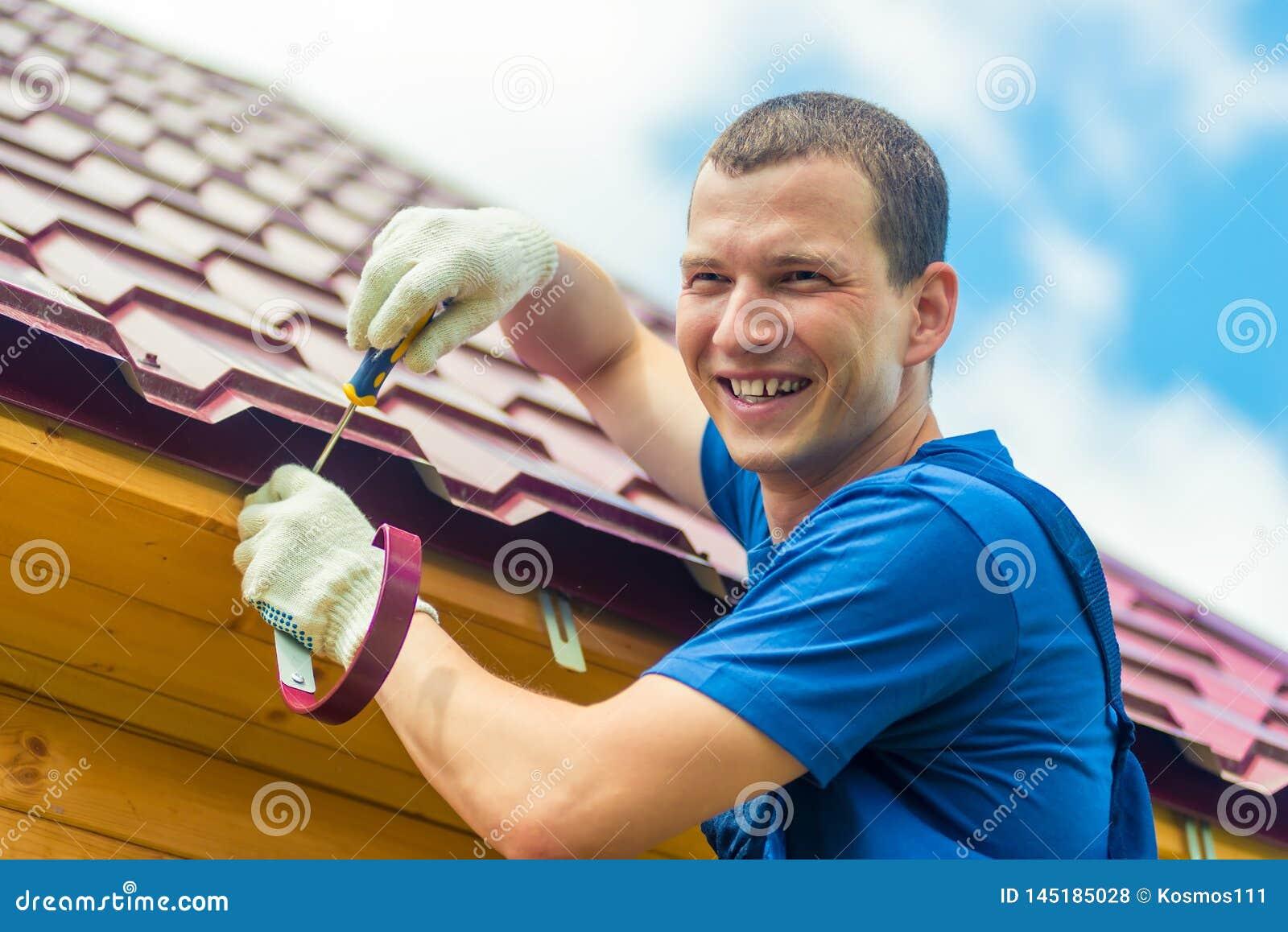 L homme heureux répare le toit de la maison, un portrait sur le fond