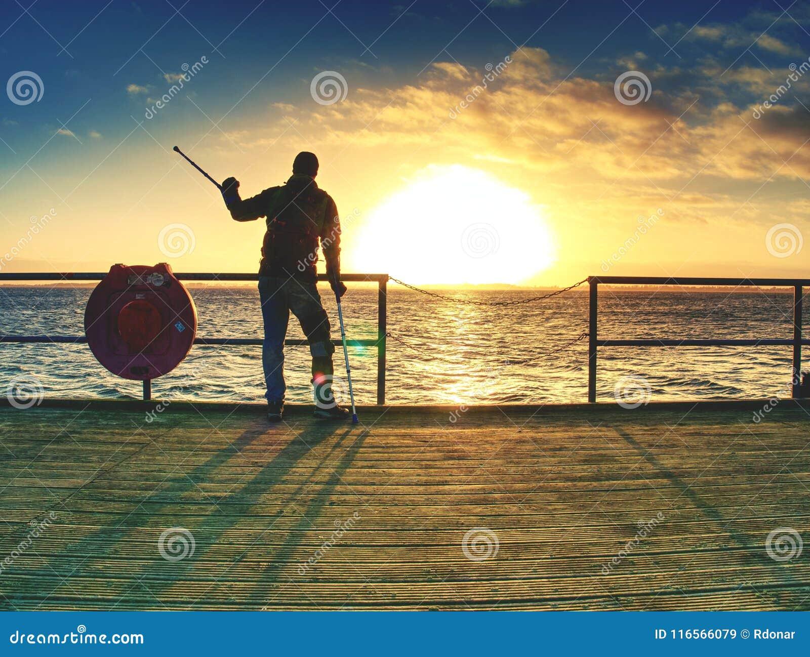 L homme heureux sur le pont tenant son avant-bras soutient Geste de liberté