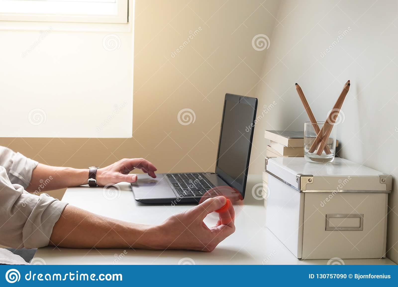 L homme hyperactif a la difficulté se concentrant tout en travaillant et jouant avec un jouet de fileur de personne remuante