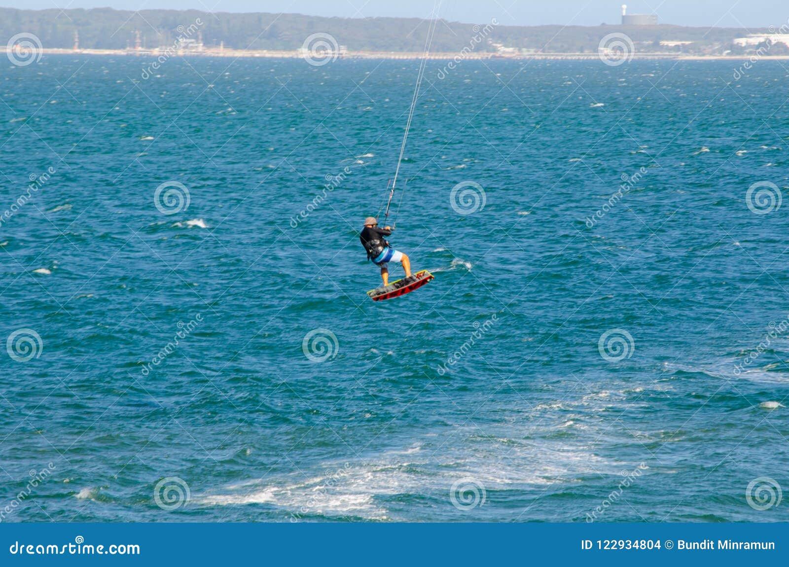 L homme jouant l action extrême en sautant au-dessus de l eau de mer avec le conseil de kitesurf dans la couleur verte à la plage