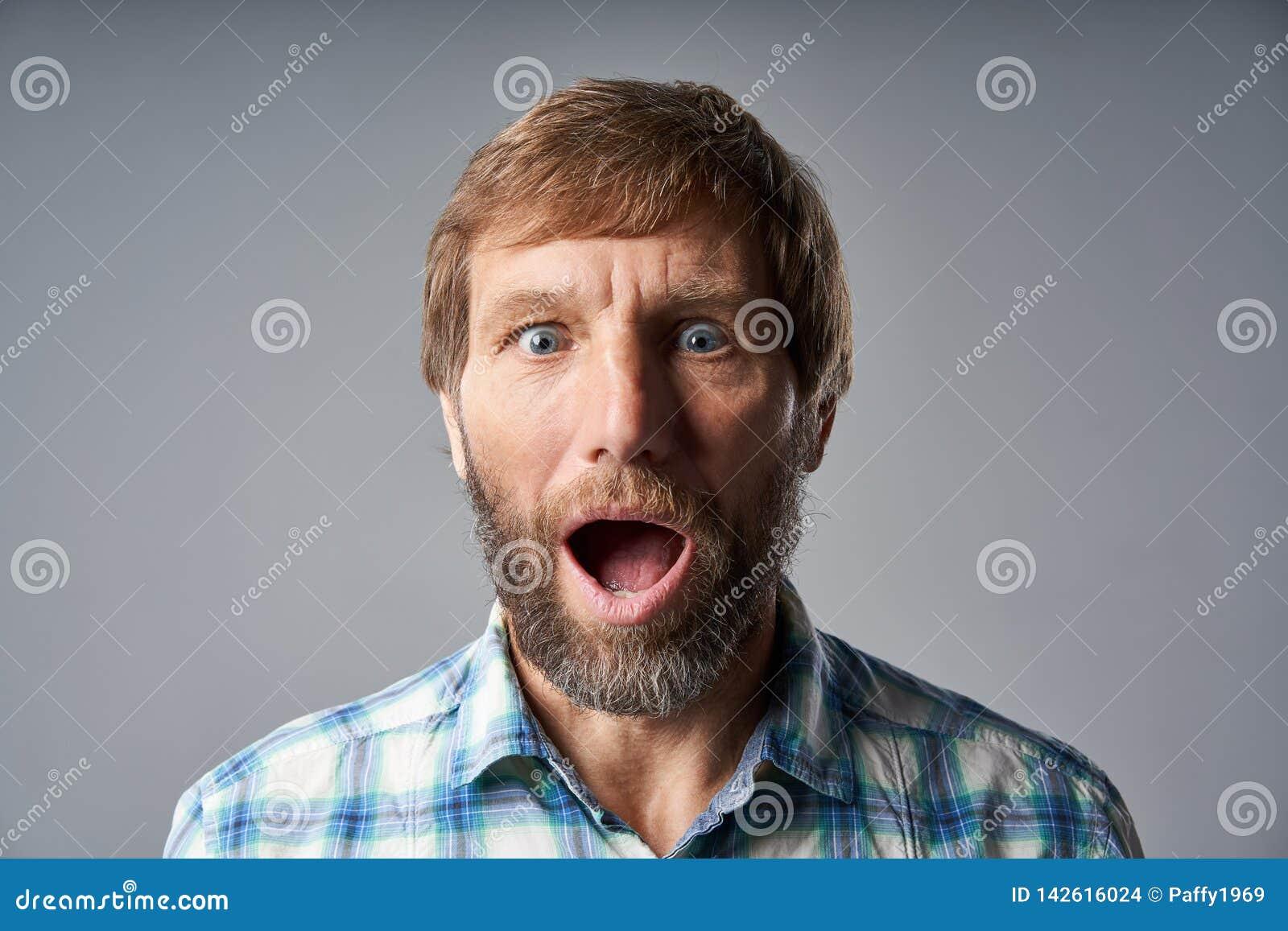 L homme mûr étonné dans la chemise à carreaux avec la bouche s est ouvert