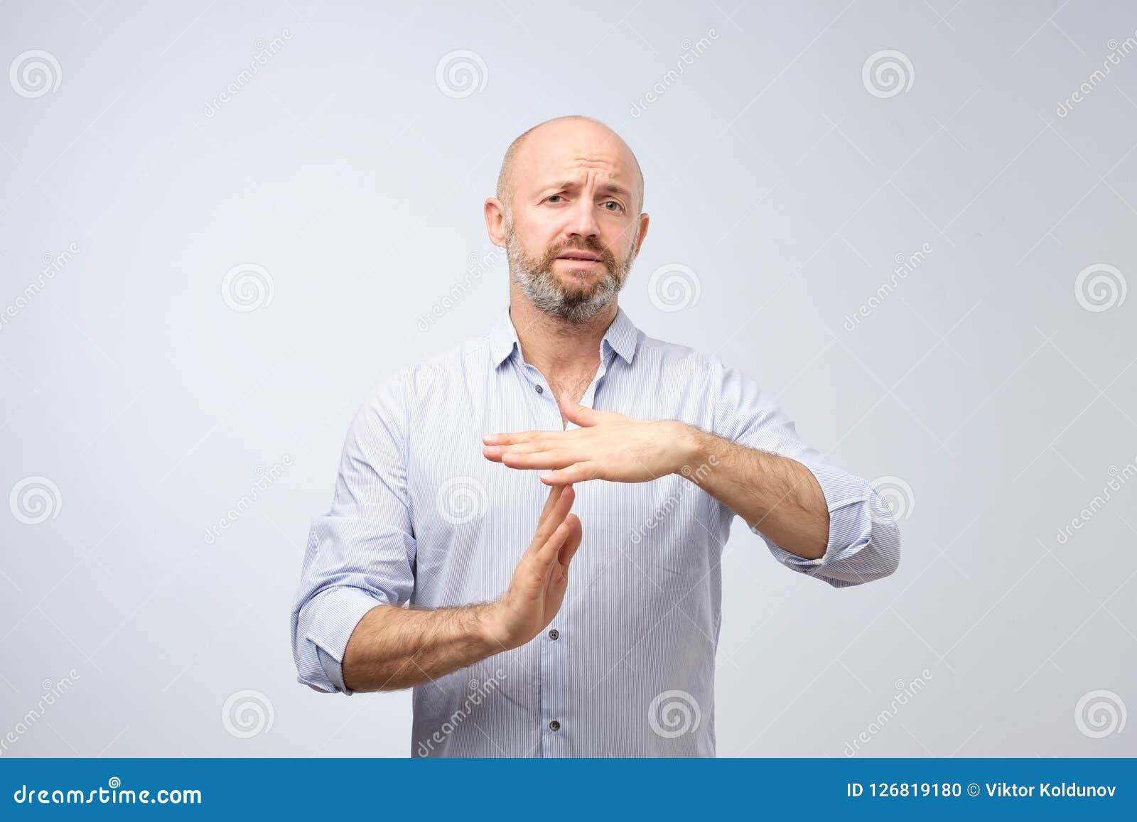 L homme mûr montrant le geste de main de temps, demandant à s arrêter a isolé sur le fond gris de mur