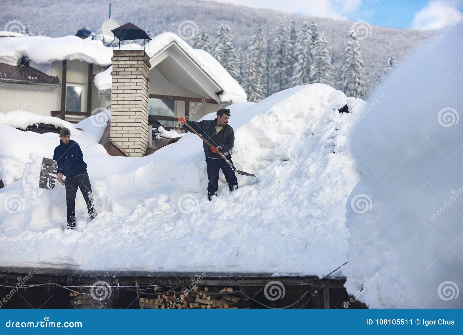 L homme nettoie le toit de la maison pendant les chutes de neige 2017