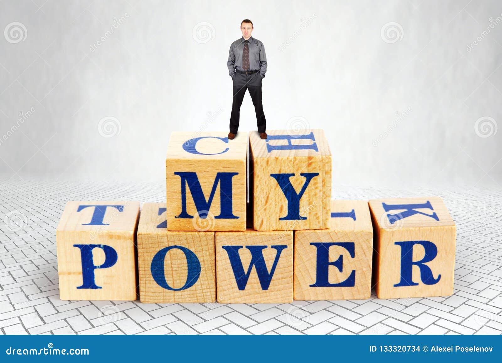 L homme plein d assurance tient sur le dessus du tas des blocs en bois avec un texte ma puissance