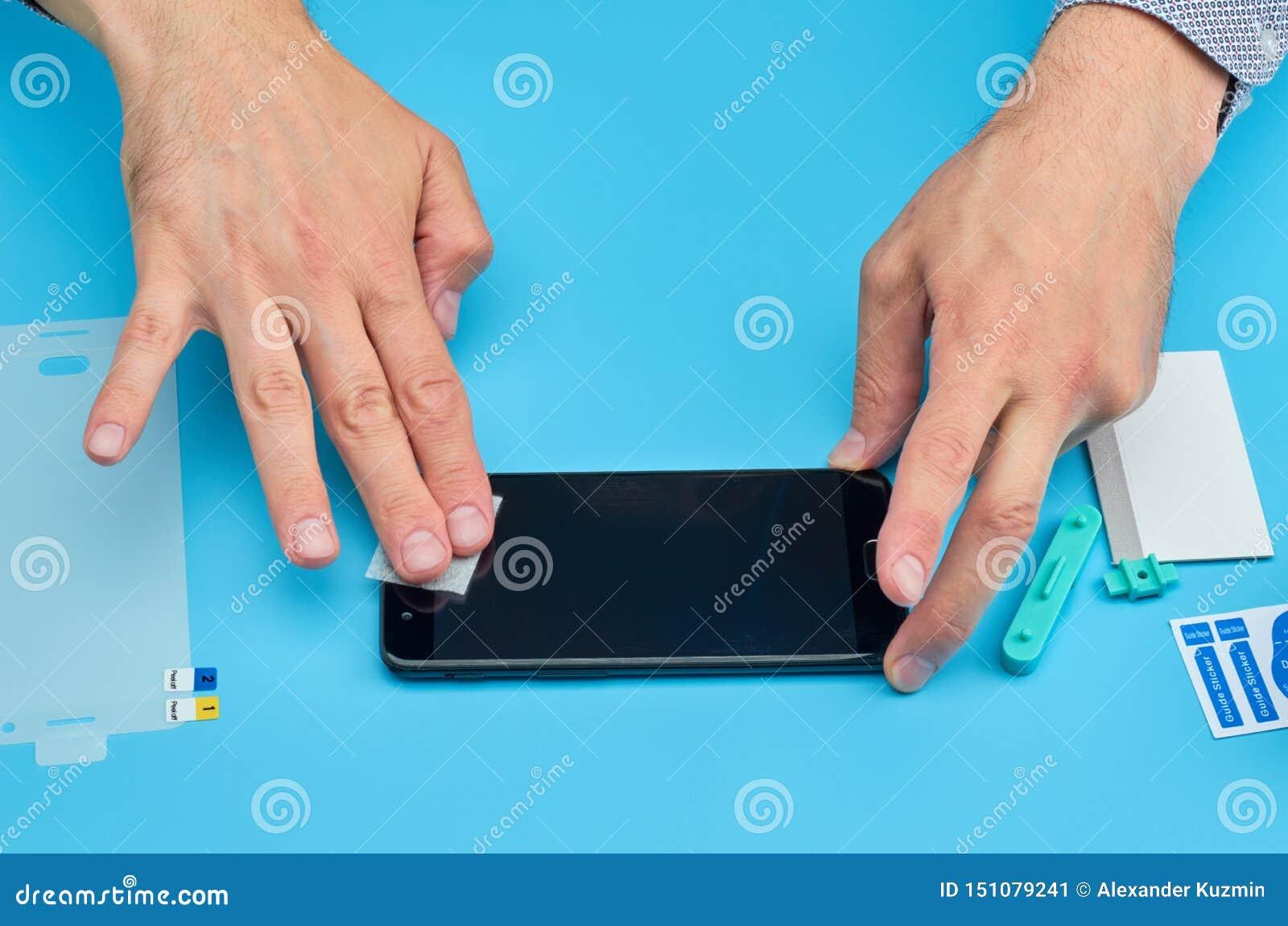 L homme remplaçant le protecteur cassé d écran de verre trempé pour le smartphone