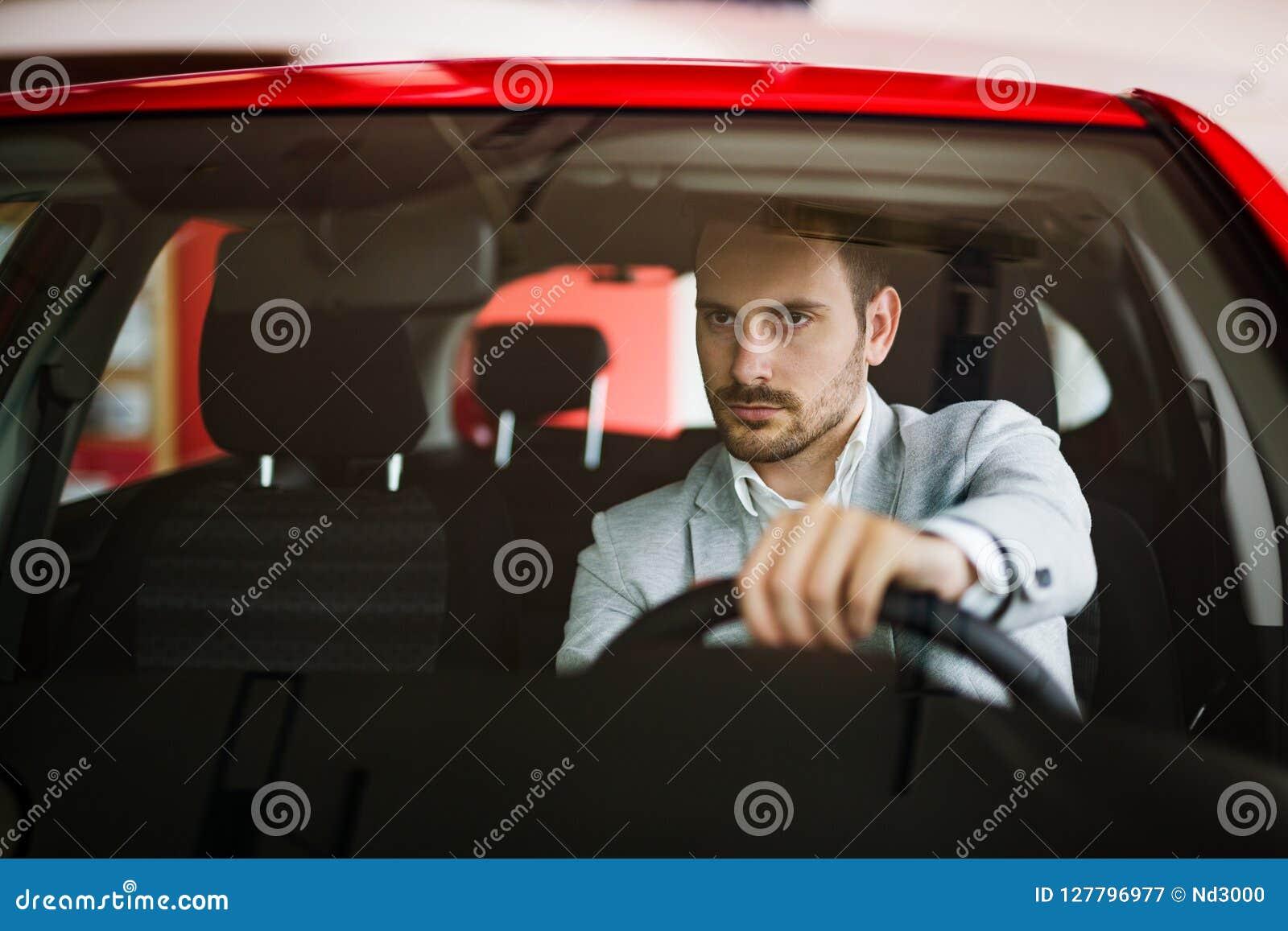 L homme sérieux élégant bel conduit une voiture moderne