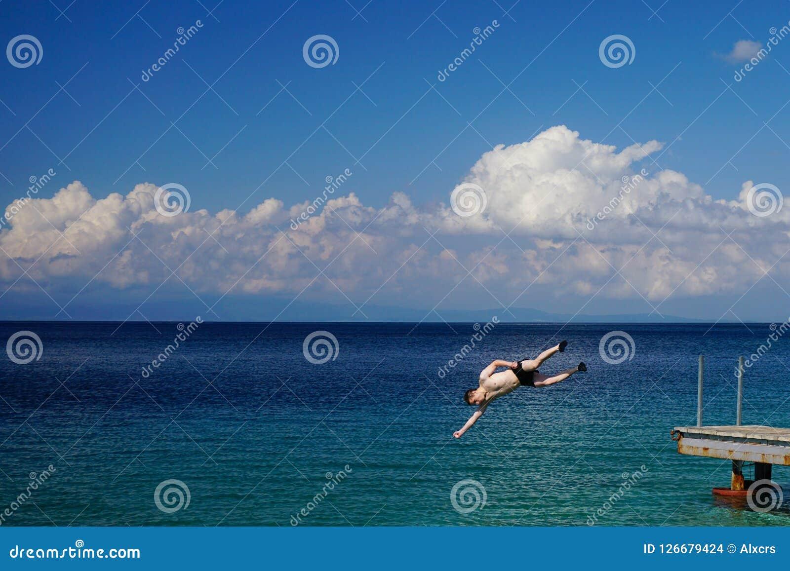 L homme sautant en mer de jetée