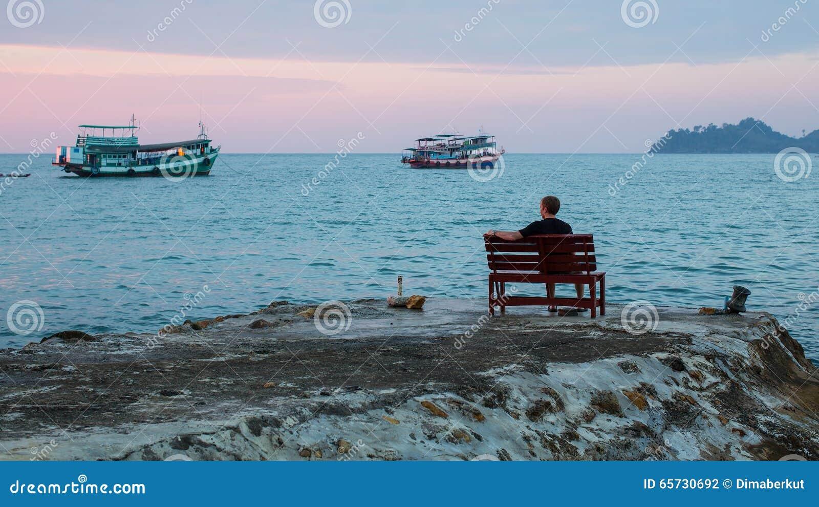 L homme seul s assied sur un banc sur la côte observant les bateaux de pêche