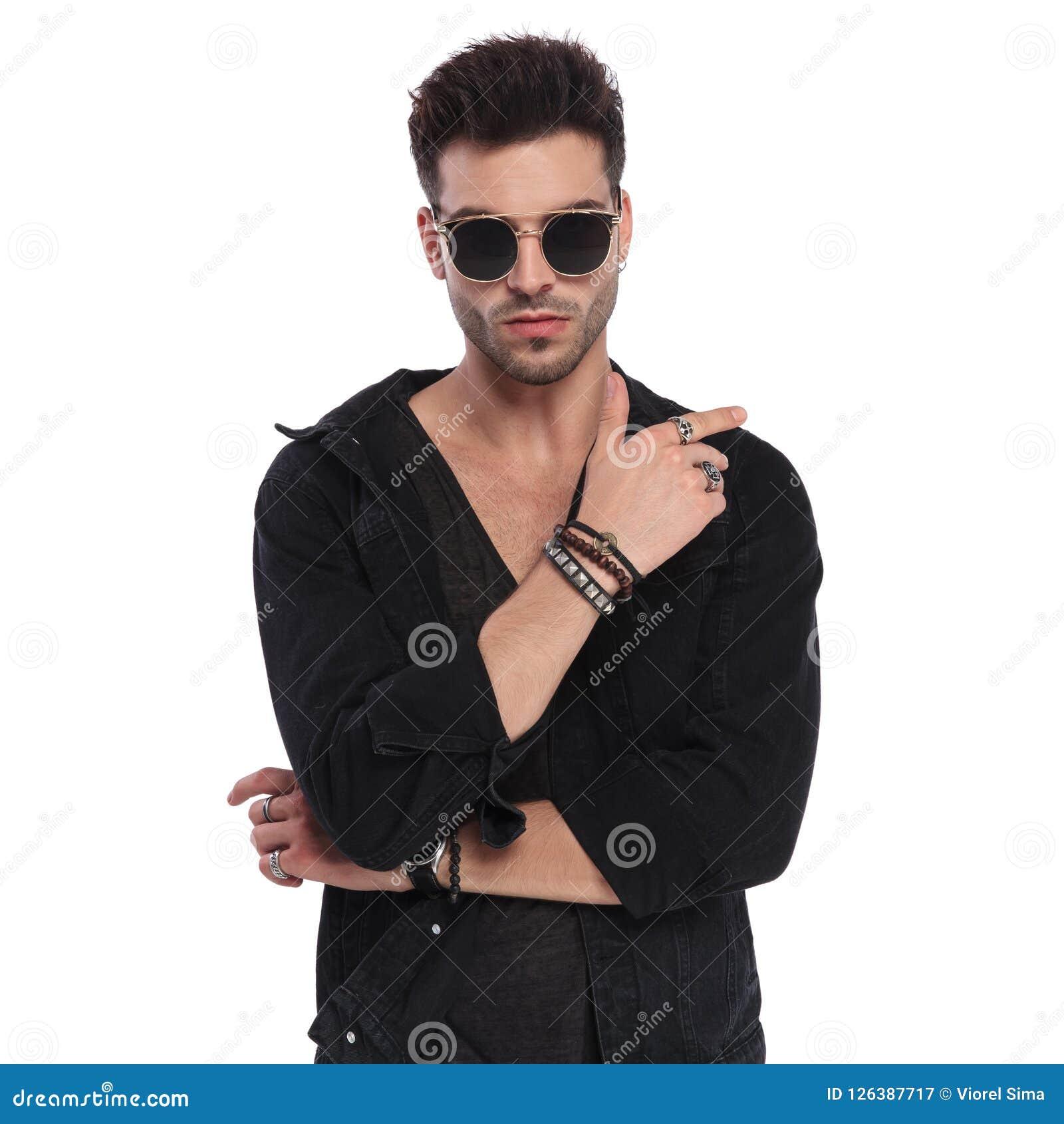 cee60556d0942 L homme sexy utilisant la chemise noire montre ses bracelets et anneaux