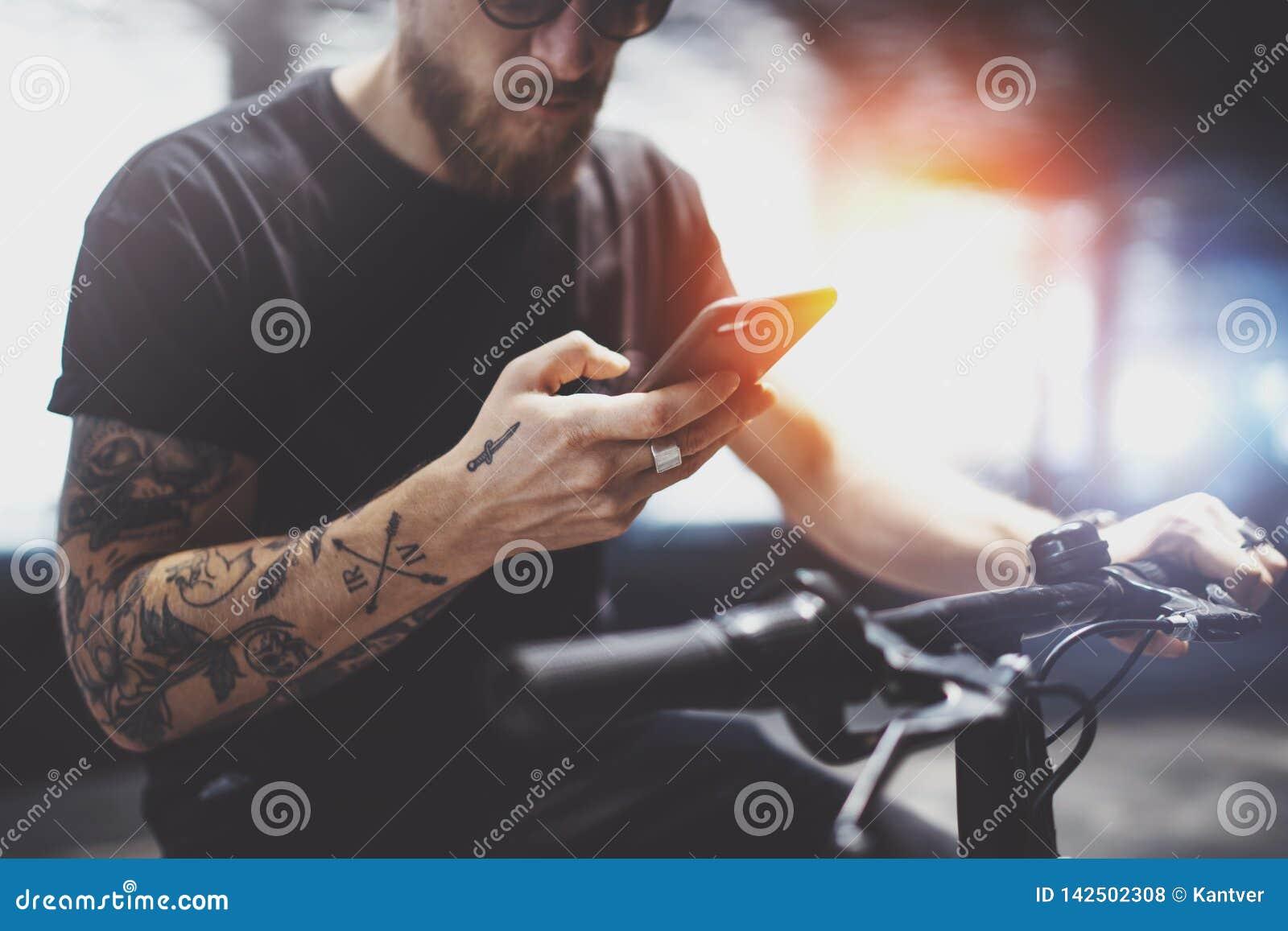L homme tatoué barbu dans des lunettes de soleil utilisant le téléphone portable pour envoient le message textuel après la monte