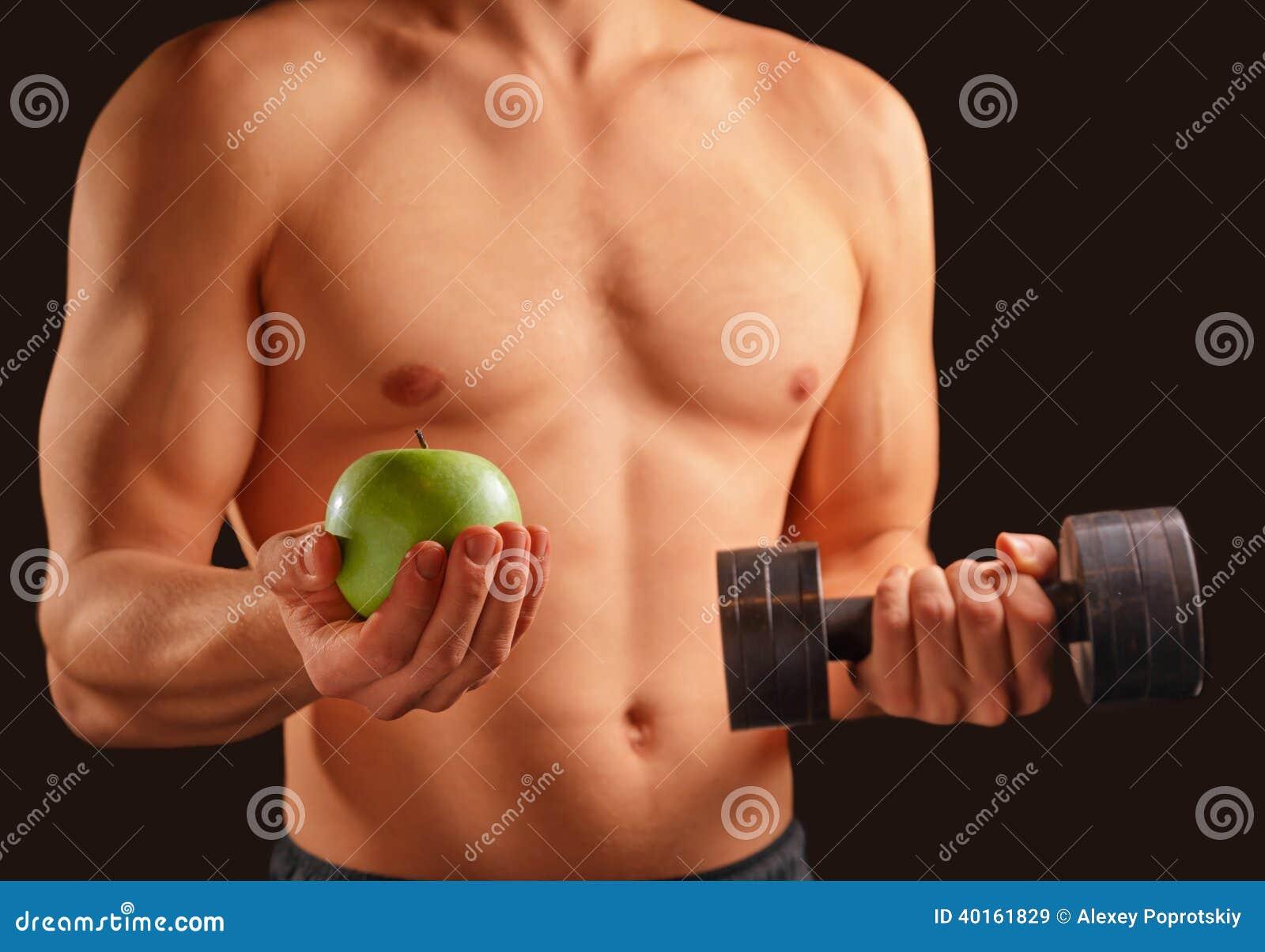 L homme tient la pomme et l haltère