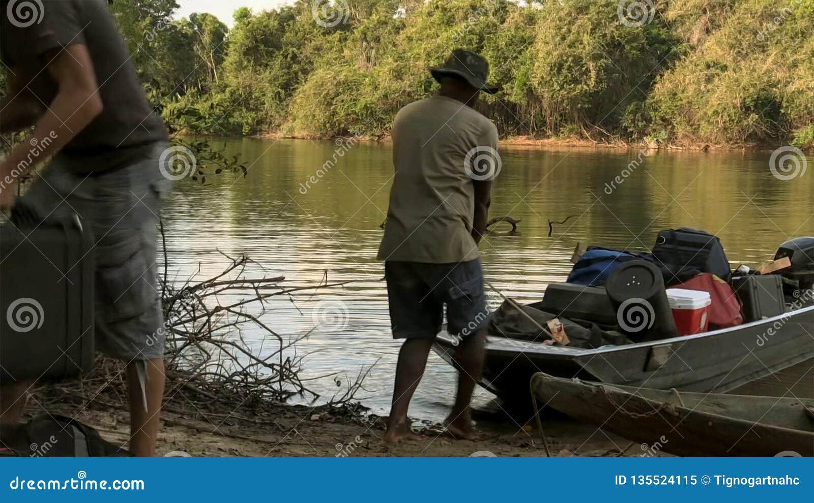 L homme traîne le bateau au-dessus du rivage de lac avec des bagages