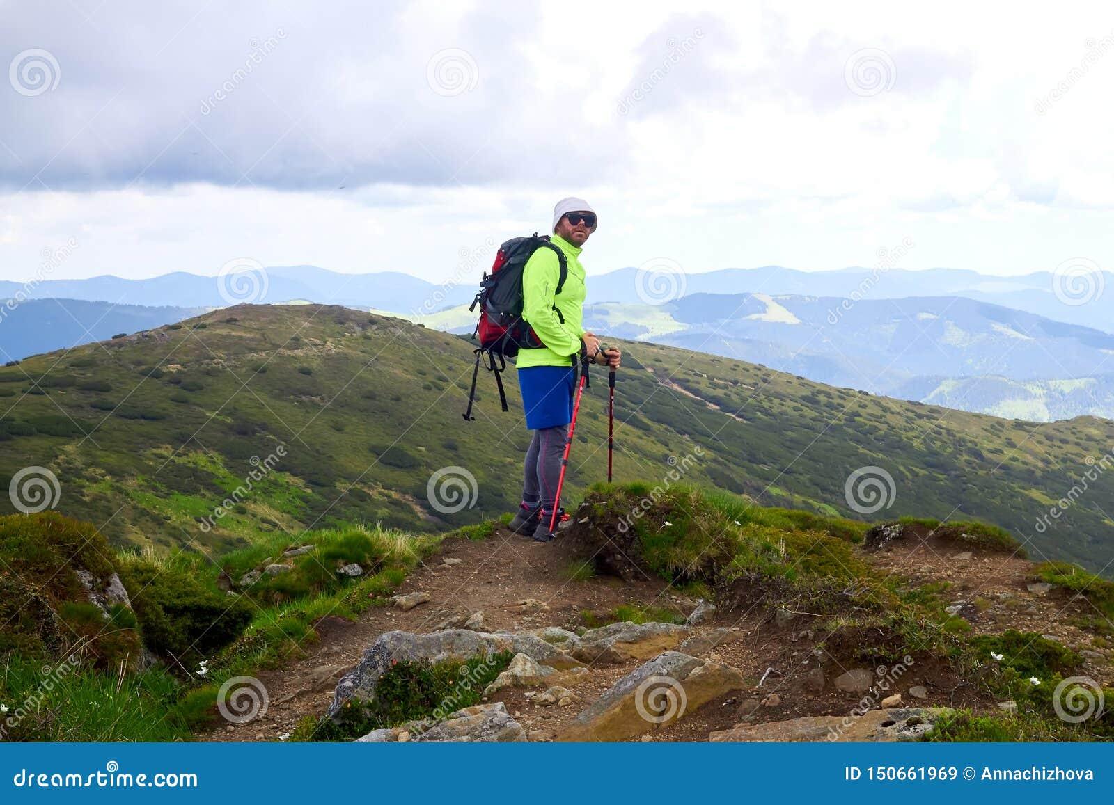 L homme voyageant avec le sac à dos augmentant en montagnes voyagent des vacances actives d aventure de concept de succès de mode