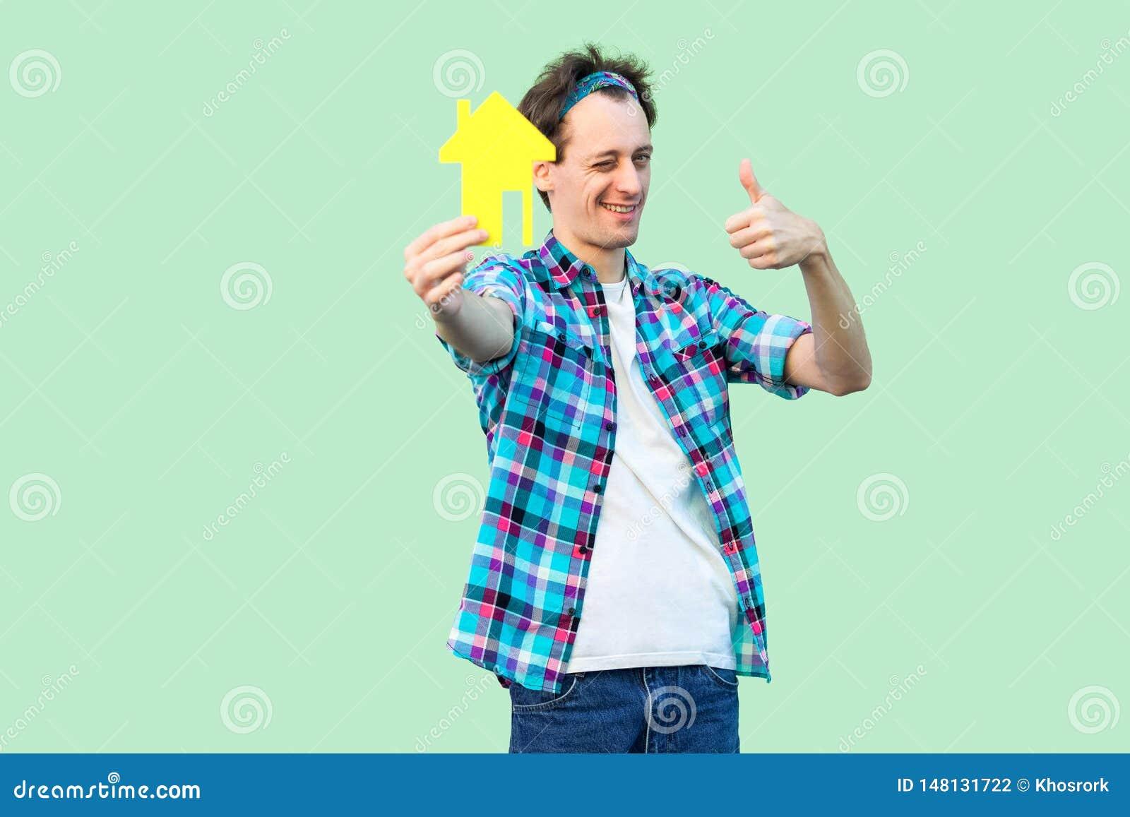 L hypothèque est bonne Jeune homme de clignotement positif dans la chemise à carreaux tenant la petite maison de papier jaune et