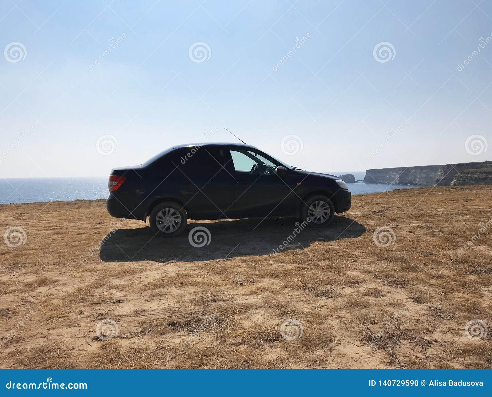 L image devant la scène de voiture de sport derrière comme soleil se couchant avec des turbines de vent dans le dos