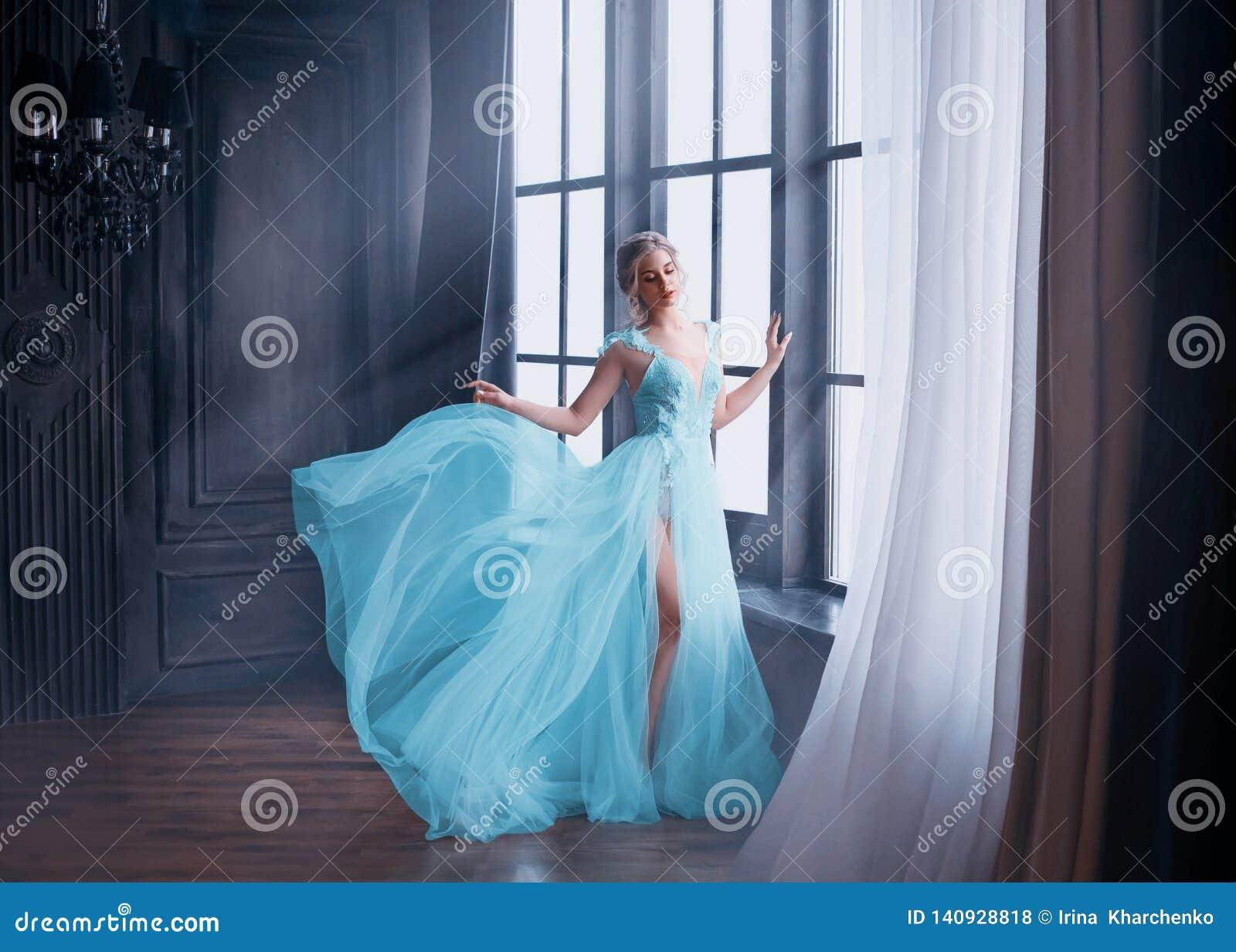 L image magnifique du diplômé en 2019, fille dans la longue robe volante douce bleue avec la jambe nue seul se tient, princesse f
