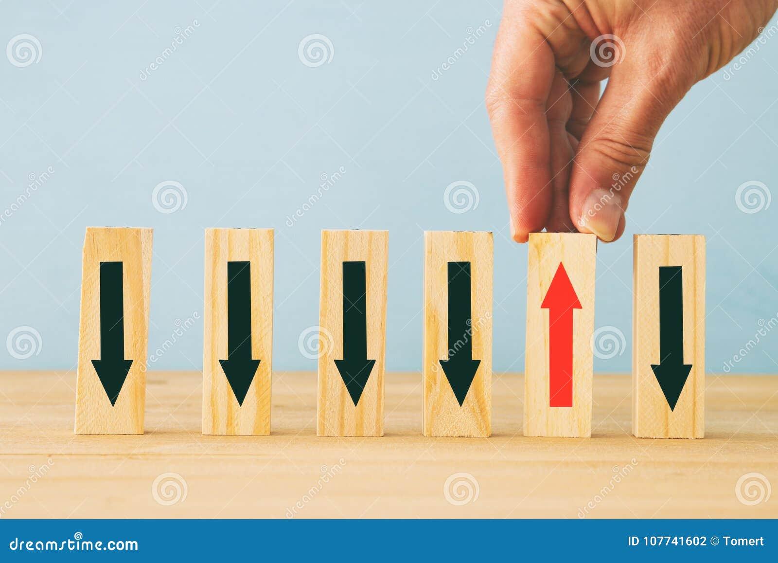 L immagine dell uomo raccoglie a mano uno da molti blocchi di legno Concetto di affari
