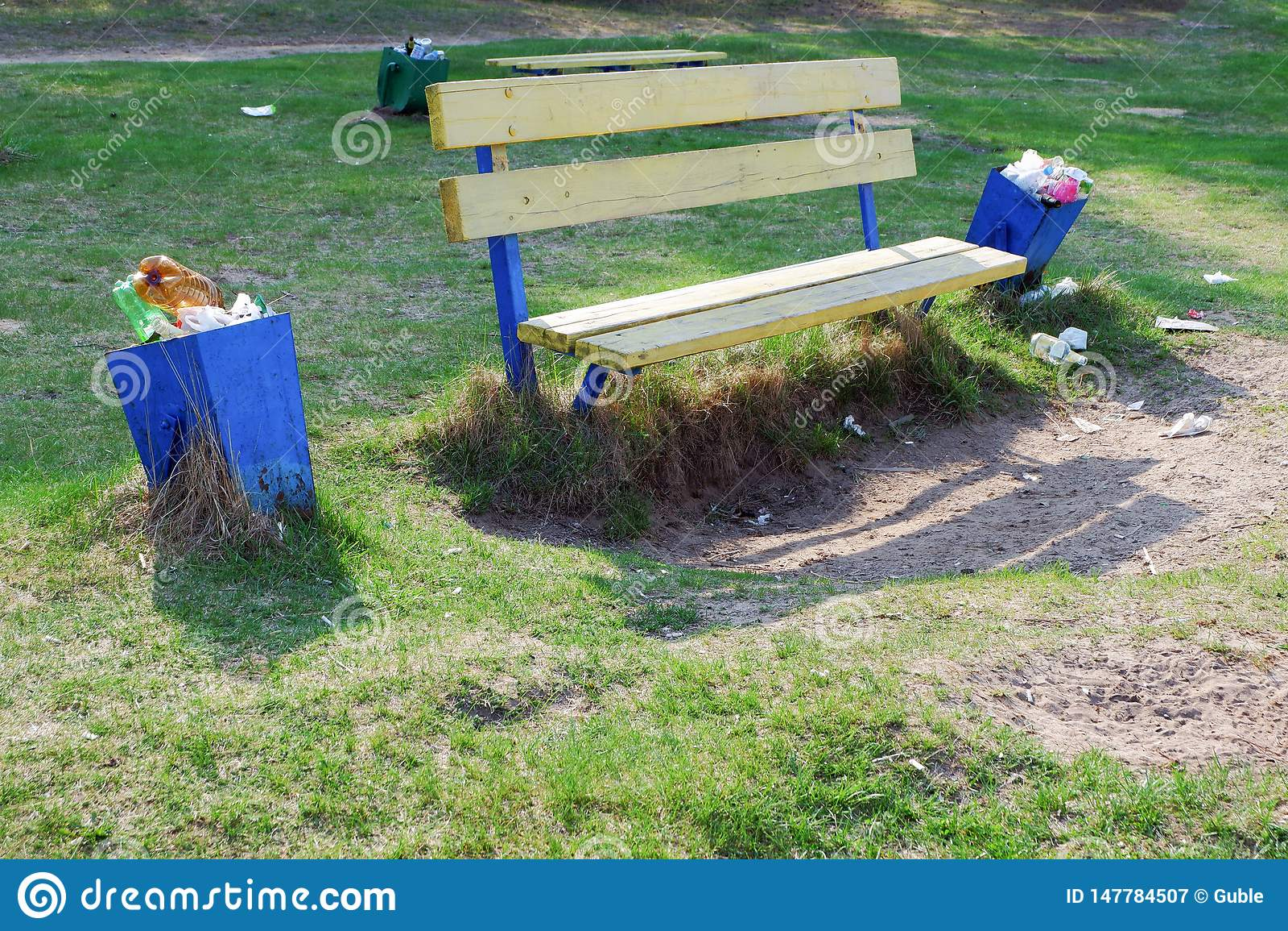 L immondizia ? accanto alla pattumiera vicino al banco in un parco Scomparto di immondizia pieno Spreco della plastica
