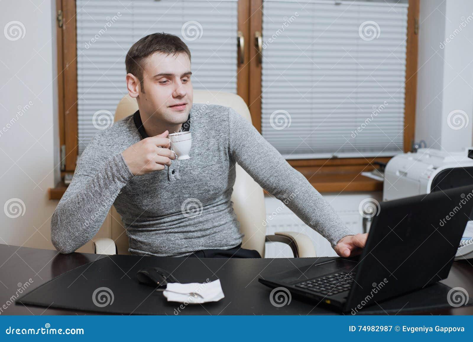L indépendant d employé de bureau s assied au bureau et à travailler à l ordinateur portable pendant la pause-café au bureau