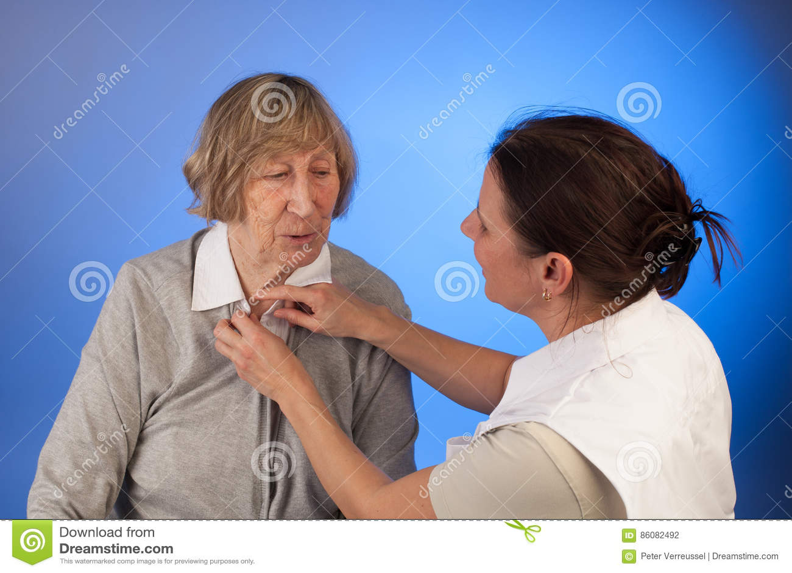 L infermiere aiuta una donna senior con vestirsi